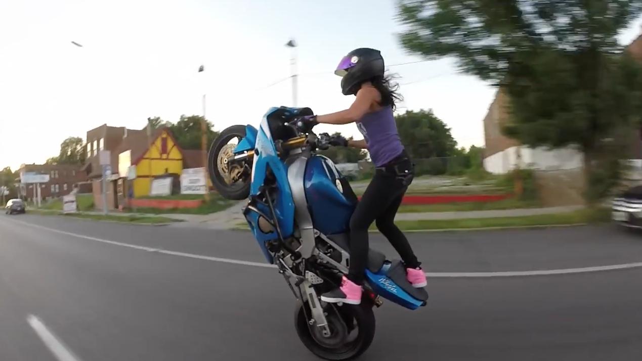 une jeune femme fait des cascades en moto en pleine ville. Black Bedroom Furniture Sets. Home Design Ideas